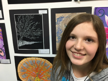 Makayla Johnson pictured with her artwork (the colorful round drawing below her)